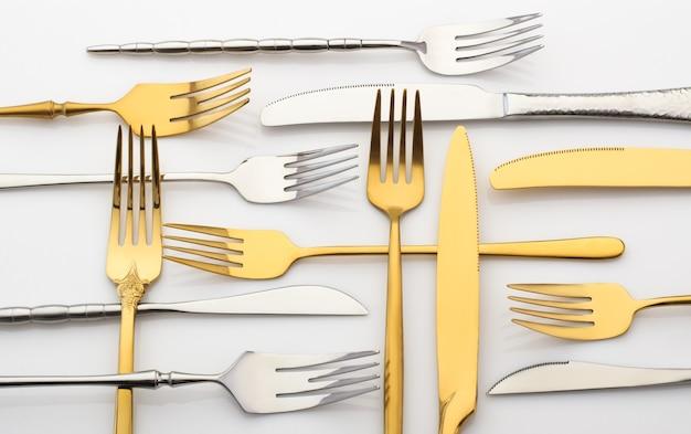 Garfos e facas de metal em uma mesa branca. conjunto de talheres de ouro e prata