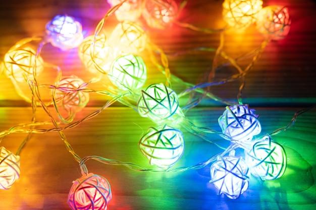 Garland, brilhando com luzes coloridas multicoloridas à noite na mesa de madeira. aventura divertida e celebração na véspera de natal ou feriado de ano novo ou carnaval festivo com luz de néon brilhante