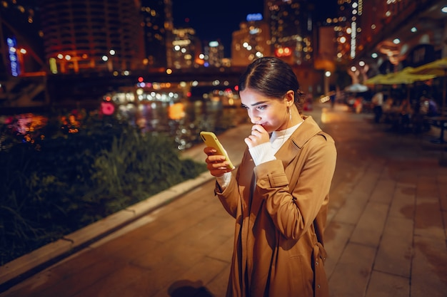Garota à noite com telefone