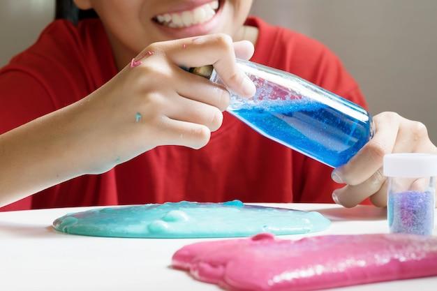 Garota abertura garrafa de cor de água usar para brinquedo caseiro chamado lodo, adolescente se divertindo e sendo criativo lodo caseiro. foco seletivo na garrafa.