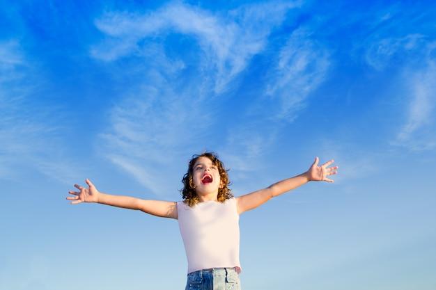Garota abre os braços ao ar livre sob o céu azul