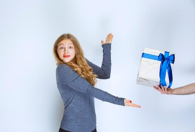 Garota abrindo as mãos e pegando a caixa de presente azul branca oferecida a ela.
