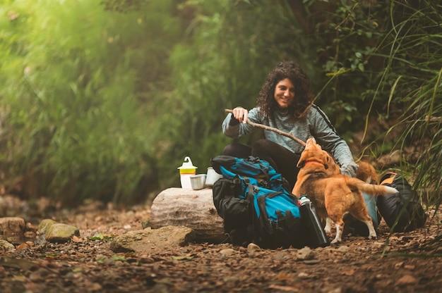 Garota acampando com seus cachorros no meio da natureza, brincando com seus cachorros.