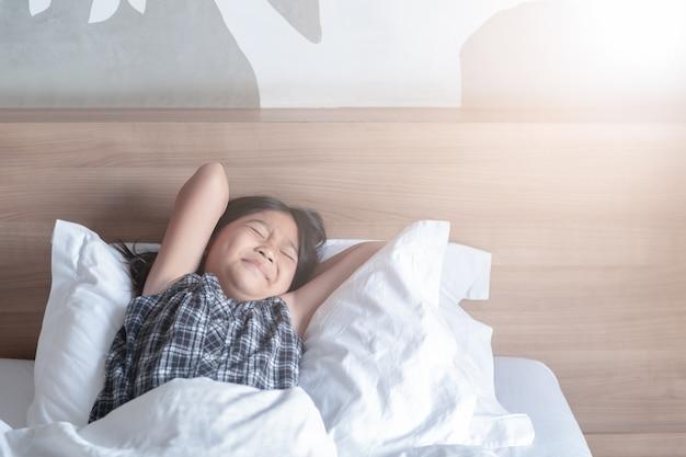 Garota acorda e estendendo-se na cama de manhã