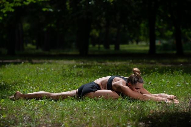 Garota acrobata executa elemento acrobático na grama do parque