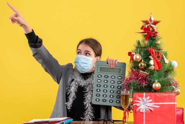 Garota admirada de vista frontal com máscara médica sentada à mesa segurando calculadora apontada com o dedo algo árvore de natal e coquetel de presentes