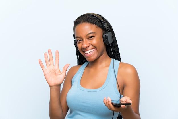 Garota adolescente afro-americana, com cabelo longo trançado, ouvindo música com um celular saudando com a mão com expressão feliz