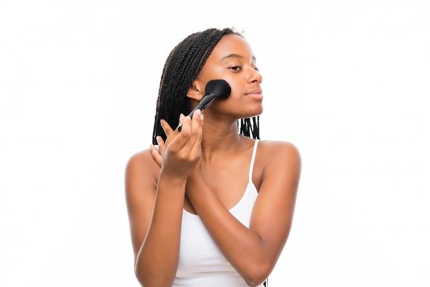 Garota adolescente afro-americana, com longos cabelos trançados com pincel de maquiagem