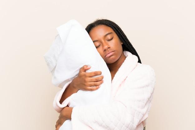 Garota adolescente afro-americana, com longos cabelos trançados de pijama sobre parede isolada