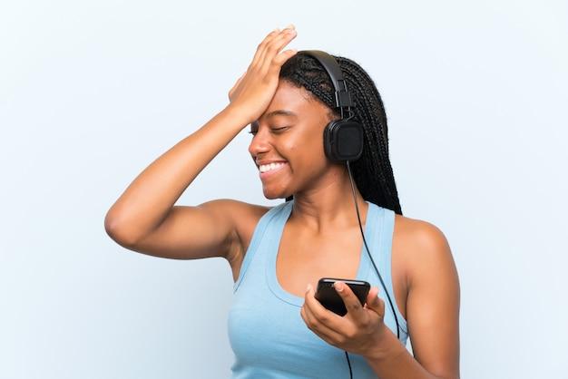 Garota adolescente afro-americana com longos cabelos trançados, ouvindo música com um celular, percebeu algo e pretendia a solução