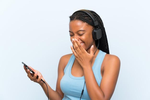 Garota adolescente afro-americana, com longos cabelos trançados, ouvindo música com um celular sorrindo muito