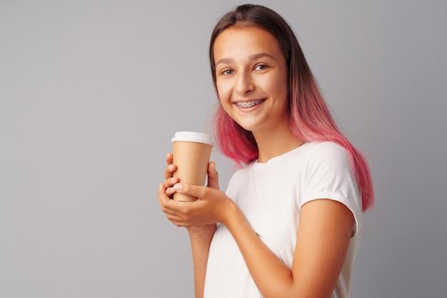 Garota adolescente agradável, segurando uma xícara de café sobre um fundo cinza
