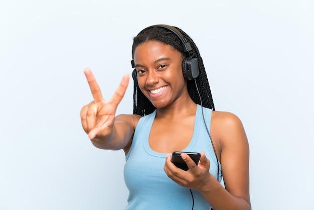 Garota adolescente americana africano com cabelo longo trançado, ouvindo música com um celular sorrindo e mostrando sinal de vitória