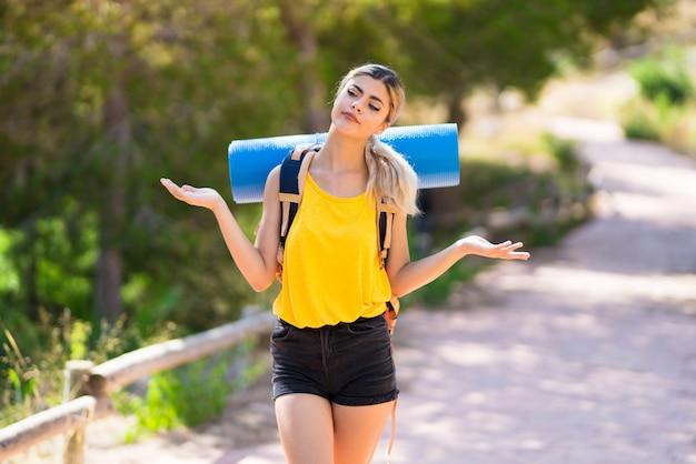 Garota adolescente, caminhadas ao ar livre, fazendo o gesto de dúvidas