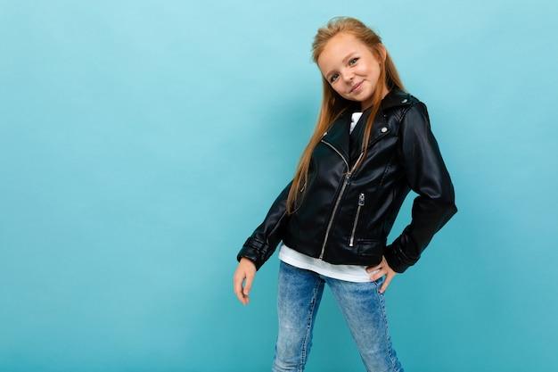 Garota adolescente caucasiano em sorrisos pretos de jaqueta e calça jeans isolados em fundo azul