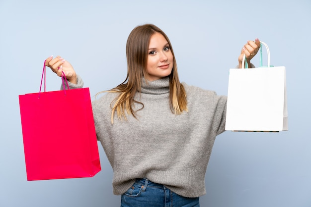 Garota adolescente com blusa segurando um monte de sacolas de compras