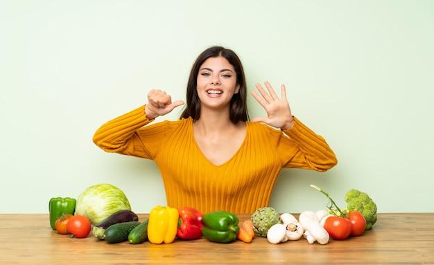 Garota adolescente com muitos legumes, contando seis com os dedos