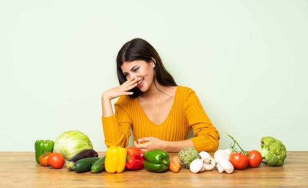Garota adolescente com muitos legumes, sorrindo muito