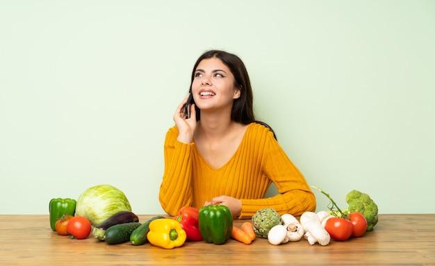 Garota adolescente com muitos vegetais, mantendo uma conversa com o telefone móvel