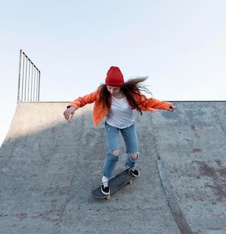Garota adolescente completa patinando