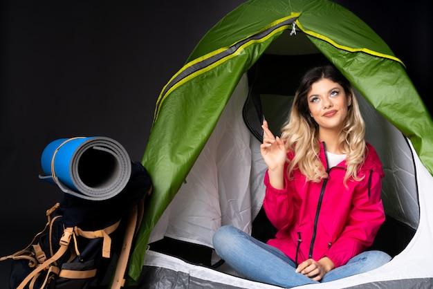 Garota adolescente dentro de uma barraca de acampamento verde na parede preta, mostrando e levantando um dedo em sinal dos melhores