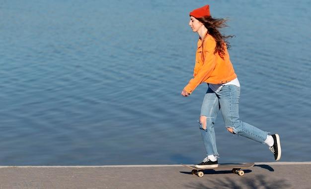 Garota adolescente em cena completa andando de skate à beira do lago