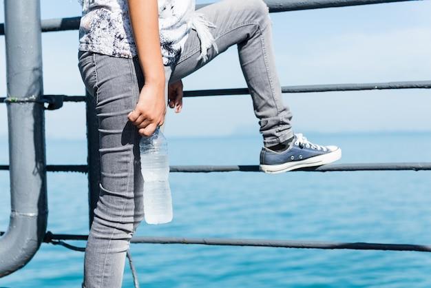 Garota adolescente em estilo único com sapato da moda tênis segurando a garrafa de água fria em dia de sol