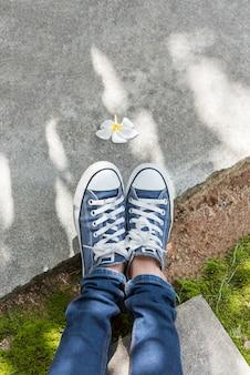 Garota adolescente em estilo único, com sapato de tênis da moda, segurando a garrafa de água fria em dia de sol