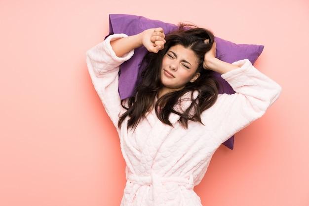 Garota adolescente em roupão sobre backgrounnd rosa e bocejando