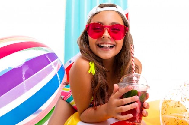 Garota adolescente em roupas de natação entre natação círculos e colchões de férias em um branco isolado