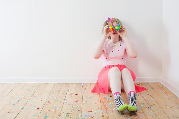 Garota adolescente em traje de palhaço, sentada no chão de madeira