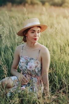 Garota adolescente em um chapéu de palha e um país vintage vestidos sentado na grama, segurando uma flor nas mãos, uma parede lateral de cesta de vime