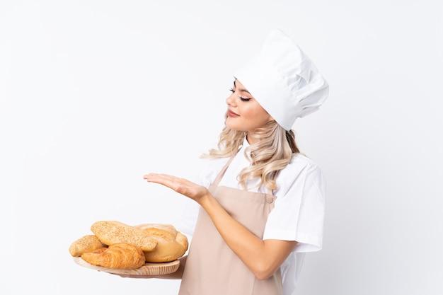 Garota adolescente em uniforme de chef. padeiro feminino segurando uma mesa com vários pães sobre branco isolado, estendendo as mãos para o lado para convidar para vir