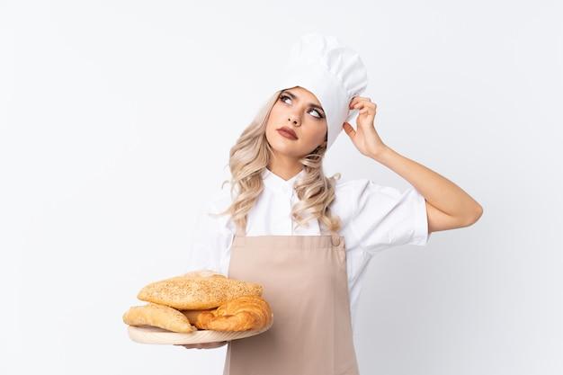 Garota adolescente em uniforme de chef. padeiro feminino segurando uma mesa com vários pães sobre branco isolado, tendo dúvidas e com a expressão do rosto confuso