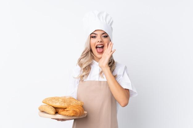 Garota adolescente em uniforme de chef. padeiro feminino segurando uma mesa com vários pães sobre fundo branco isolado, gritando com a boca aberta