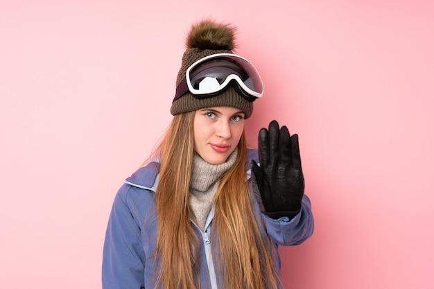 Garota adolescente esquiador com fundo de óculos de snowboard, fazendo o gesto de parada com a mão