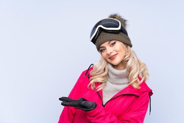 Garota adolescente esquiador com óculos de snowboard, estendendo as mãos para o lado para convidar para vir