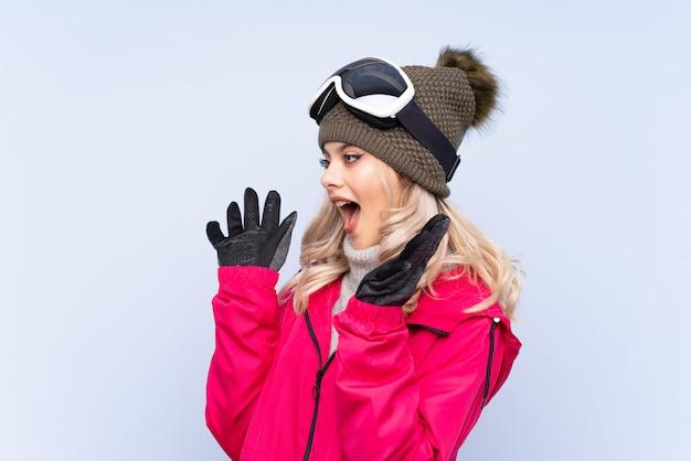 Garota adolescente esquiador com óculos de snowboard sobre fundo azul isolado com expressão facial de surpresa