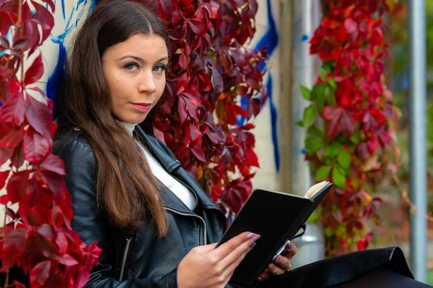 Garota adolescente glamour positiva com livro preto em uma parede de hera vermelha