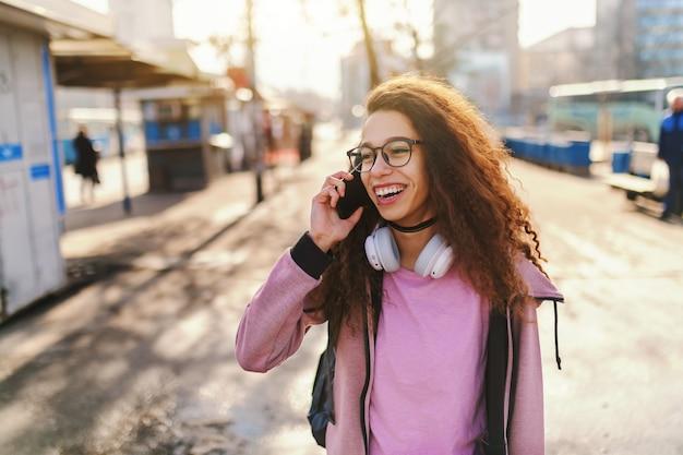 Garota adolescente hipster de raça mista com sorriso e mochila nas costas, falando ao telefone em pé na rua.