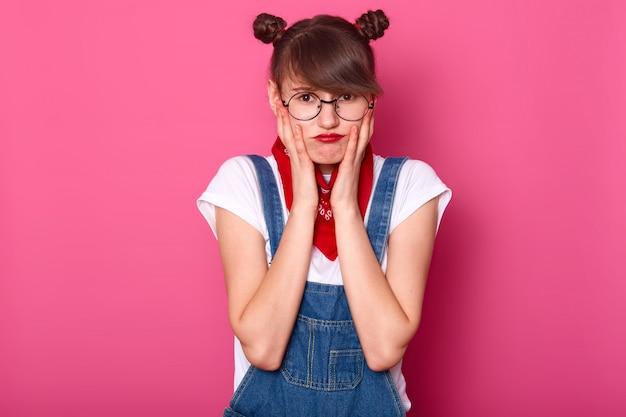 Garota adolescente infeliz ofendida com lábios carnudos, mantém as mãos nas bochechas, descontente com tudo, sente-se frustrada e chateada, modelo posa sobre rosa, copie o espaço para seu texto.