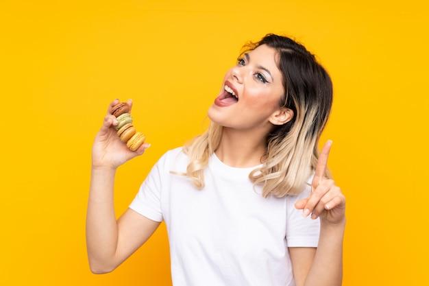 Garota adolescente isolada na parede amarela segurando macarons franceses coloridos e apontando uma ótima idéia