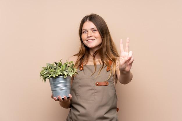 Garota adolescente jardineiro segurando uma planta sorrindo e mostrando sinal de vitória