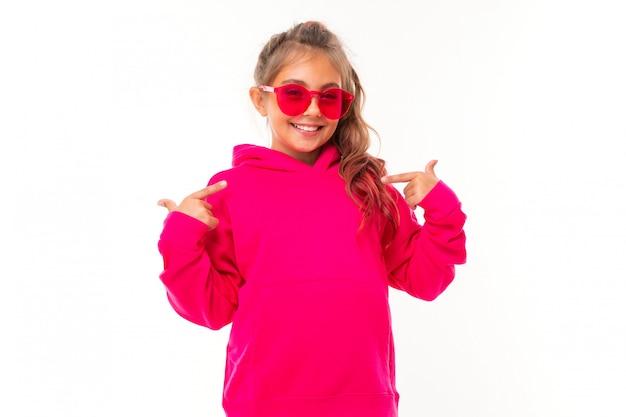 Garota adolescente na moda em rosa com capuz e com óculos de sol rosa gesticula na parede branca