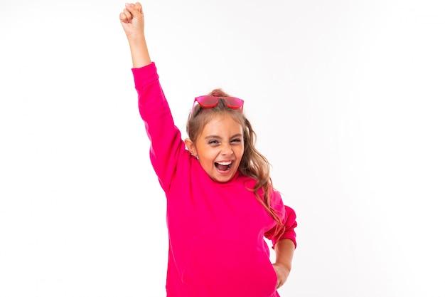 Garota adolescente na moda em rosa com capuz e com óculos de sol rosa gesticula