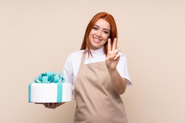 Garota adolescente ruiva com um bolo grande sobre parede isolada, sorrindo e mostrando sinal de vitória