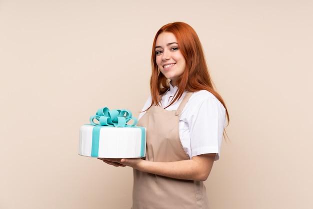 Garota adolescente ruiva com um bolo grande, sorrindo muito