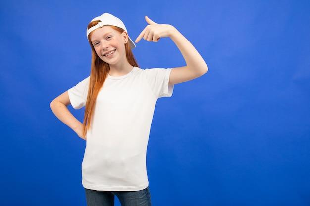 Garota adolescente ruiva em uma camiseta branca com um layout mostra a classe azul