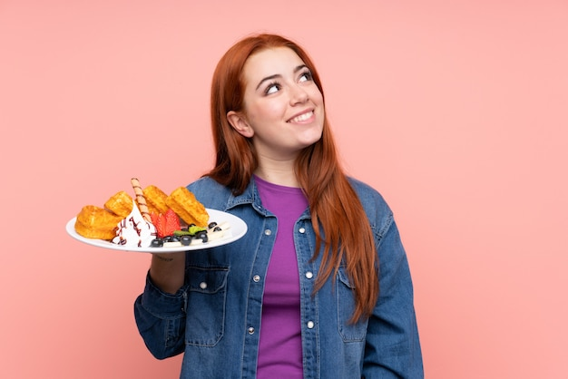 Garota adolescente ruiva segurando waffles sobre parede rosa isolada, olhando para cima enquanto sorrindo