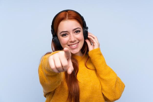 Garota adolescente ruiva sobre música de parede azul isolado e apontando para a frente